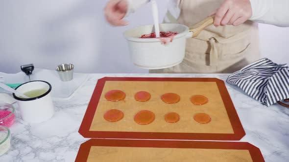 Schritt für Schritt. Gießen von karamellisiertem Zucker auf eine Silikon-Backmatte, um hausgemachte Lutscher zu machen.