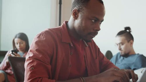 African American Man in Casualwear Working on Laptop at Office Desk