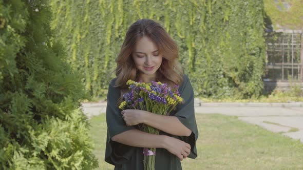 Portrait of Pretty Smiling Young Woman Holding Bouquet of Wild Flowers Looking at Camera