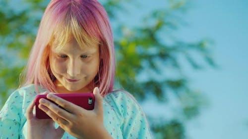 Ein Mädchen mit rosa Haar verwendet ein rosa Smartphone