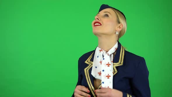 Thumbnail for A Young Beautiful Stewardess Watches a Plane Fly By - Green Screen Studio