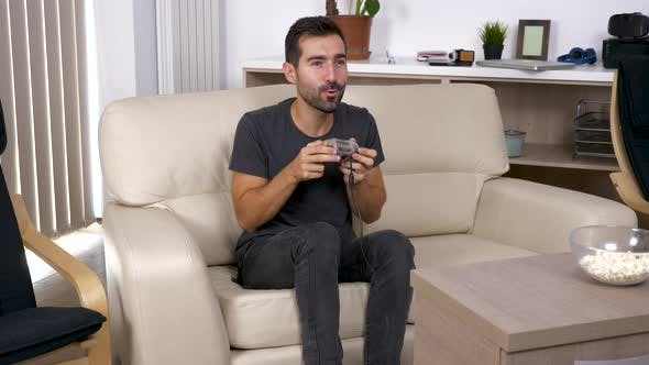 Thumbnail for Adult Man Plays a Video Game on the Console in the Living Room