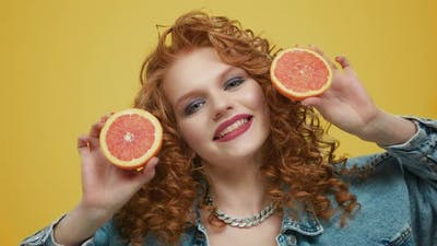 Woman Holding Grapefruit Pieces. Girl Covering Face with Grapefruit Halves