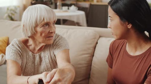 Cheerful Senior Woman Speaking with Female Caregiver