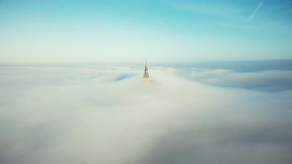Drone Rising Above Mont Saint Michel Castle Spire Covered By Ethereal Atmospheric Fog Mist Clouds in