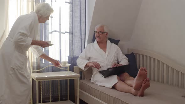 Thumbnail for Senior Caucasian Man Working on Laptop in Hotel and Wife Bringing Coffee
