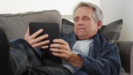 Elderly man falls asleep with tablet