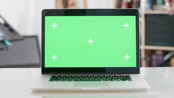 Cover Image for Green Screen on a Laptop Display on a Blured Background