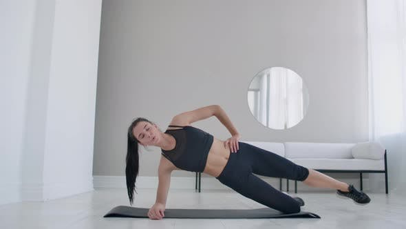 Thumbnail for The Brunette in the Apartment Does an Exercise Lateral Plank Standing on Her Knee