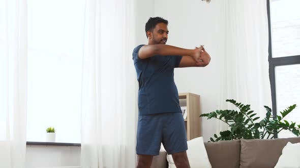 Thumbnail for Man with Fitness Tracker Stretching Waist at Home