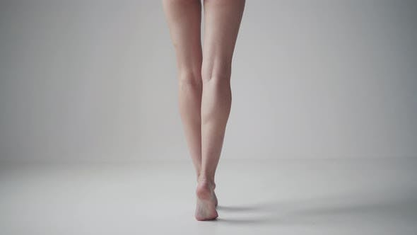 Thumbnail for Female Legs Close Up. Back View. Girl Standing on Tiptoes Barefoot on a White Background