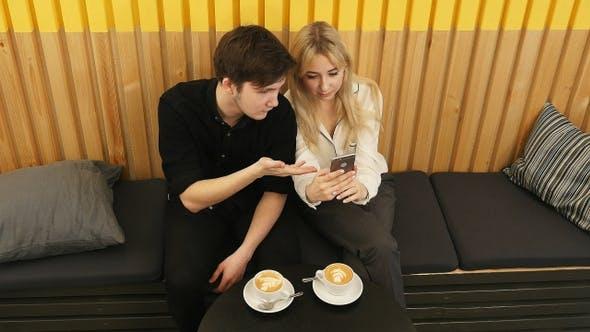Thumbnail for Glückliches Paar mit Smartphone zusammen und trinken Kaffee im Café