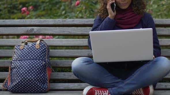 Thumbnail for Smiling Biracial Woman Sitting on Bench, Holding Laptop and Talking on Cellphone