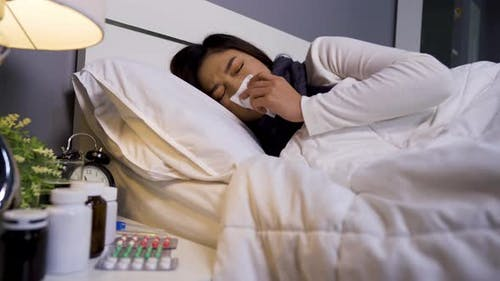 sick woman feeling cold and sneezing in bed