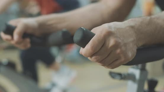 Thumbnail for Close-up of Male Caucasian Hands Putted on Handlebar of Exercise Bike in Gym. Unrecognizable Young