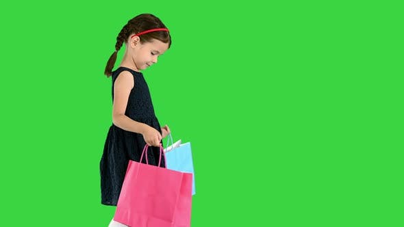 Thumbnail for Beautiful Little Girl in Black Dress Walking with Shopping Bags on a Green Screen, Chroma Key