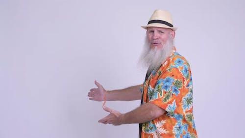 Happy Mature Bearded Tourist Man Showing Something