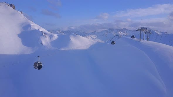 Aerial drone view of a ski gondola lift and mountains at a ski resort.