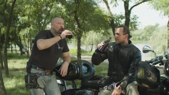 Cover Image for Brutal Bikers Drinking Beer Near Motorbike in Park