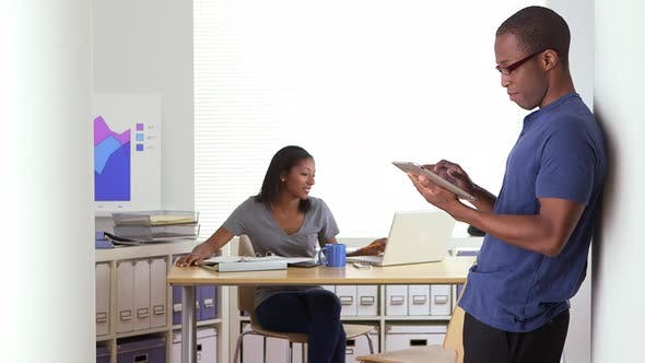 Thumbnail for Black business co workers talking while one uses tablet computer