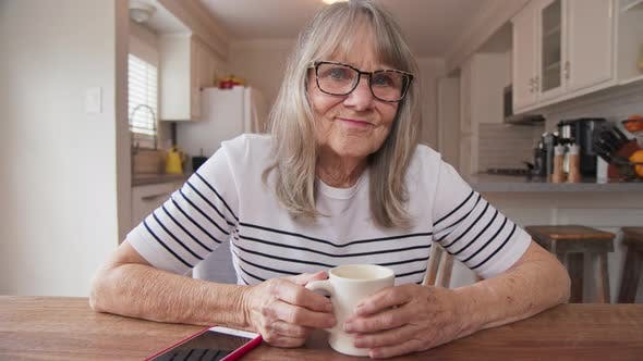 Thumbnail for Happy Senior woman smiling at camera with her morning coffee at kitchen table