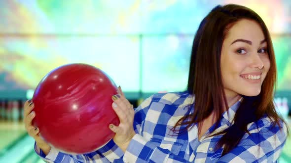 Thumbnail for Girl Holds Bowling Ball Near Her Face