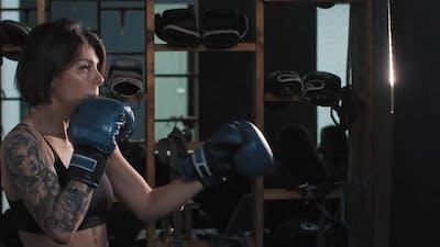 Boxing  a Tattooed Woman Punching the Punching Bag
