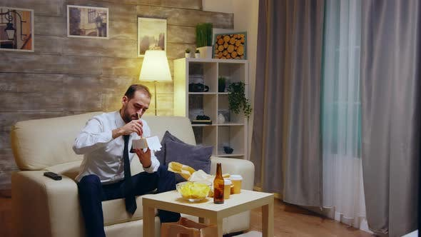 Thumbnail for Businessman Sitting on Couch Eating Takeaway Noodles From Box