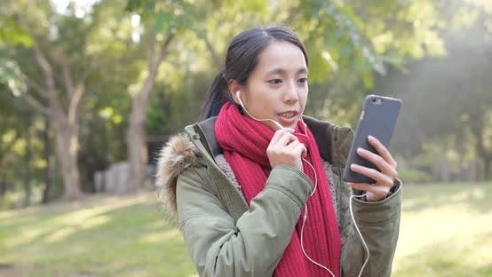 Thumbnail for Woman making live stream on smart phone in city park