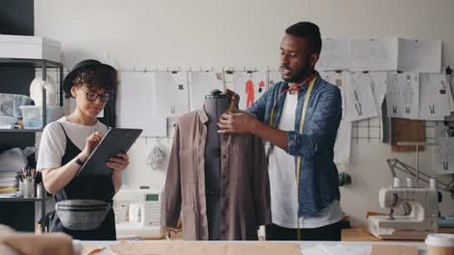 Tailor Measuring Clothes on Mannequin While Girl Colleague Working with Tablet