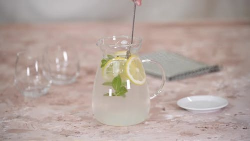 Female Hands Stirring a Lemonade with Spoon