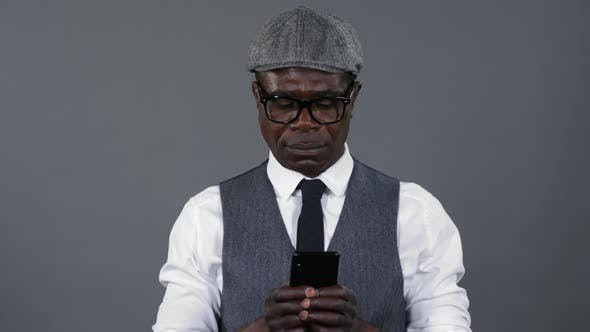 Thumbnail for Elegant African Man Typing on Smartphone