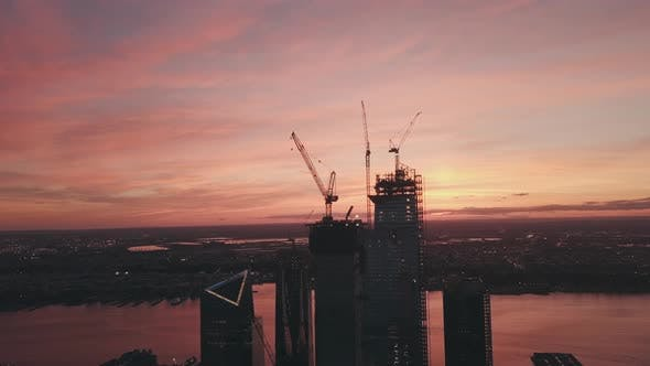 AERIAL: Manhattan, New York City High Rise Construction Site Crane in Red Dawn Sunset Light