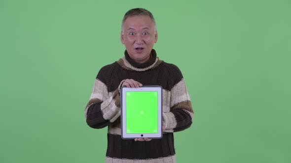 Thumbnail for Happy Mature Japanese Man Thinking While Showing Digital Tablet and Talking