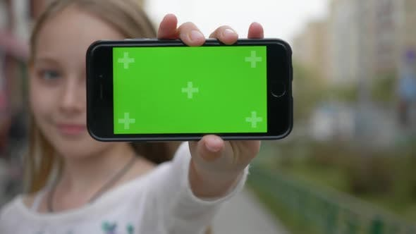 Thumbnail for Teenager Girl Showing Mobile Phone with Green Screen To Camera on City Street. Close Up Girl