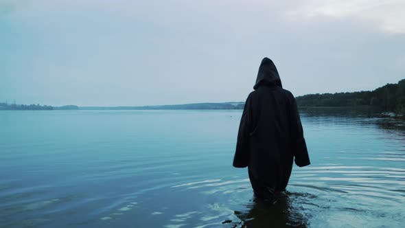 Thumbnail for Female Figure in a Black Robe Enters the Water