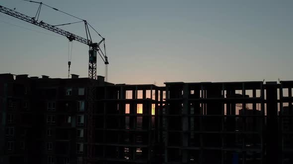Thumbnail for Aerial Drone View of silhouetteConstruction Cranes in Sunset Light. Construction Site Building
