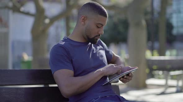 Thumbnail for Afro-American Muscular Man on Bench in Park Typing on Tablet