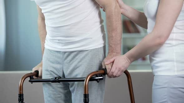 Thumbnail for Caring wife helping ill husband to move with walking frame, rehabilitation