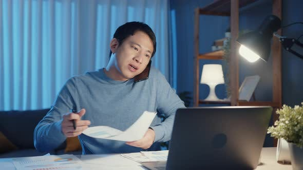 Young Asia businessman use smartphone call meeting agenda assignment paperwork.