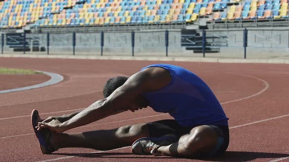 Thumbnail for Hispanic Athlete Warming His Back Doing Flexibility Exercises on Race Track