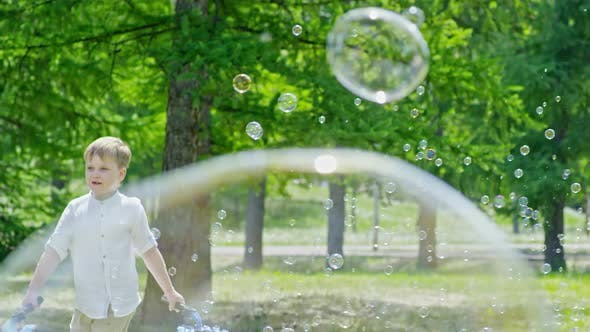 Thumbnail for Little Kid Blowing Soap Bubbles in Park with Friends