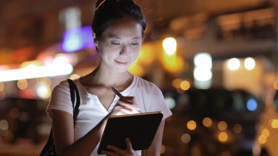 Woman using digital tablet with pen at night