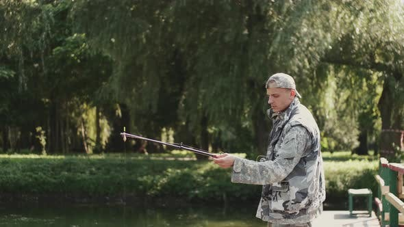 Thumbnail for Confident Fisherman Preparing a Rod for Fishing at the Pond