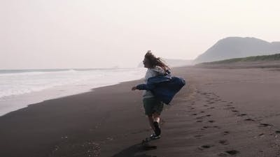 Young Woman Runs on a Black Volcanic Beach Along the Ocean