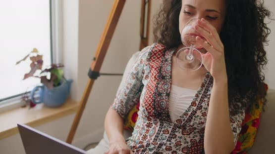 Woman drinking wine and working at home