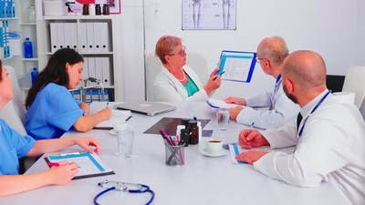 Medical Nurse Writing on Clipboard During Healthcare Seminar