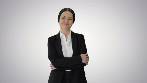 Confident Young Businesswoman Posing with Crossed Arms on Gradient Background.
