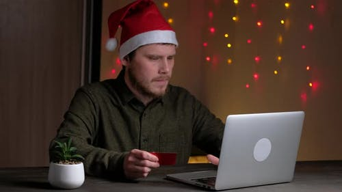 Person Holding Credit Card and Using Laptop in Home at Night