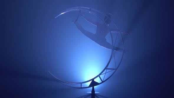 Cover Image for Gymnast in a Brilliant Costume Performs Tricks on a Special Design . Blue Smoke Background